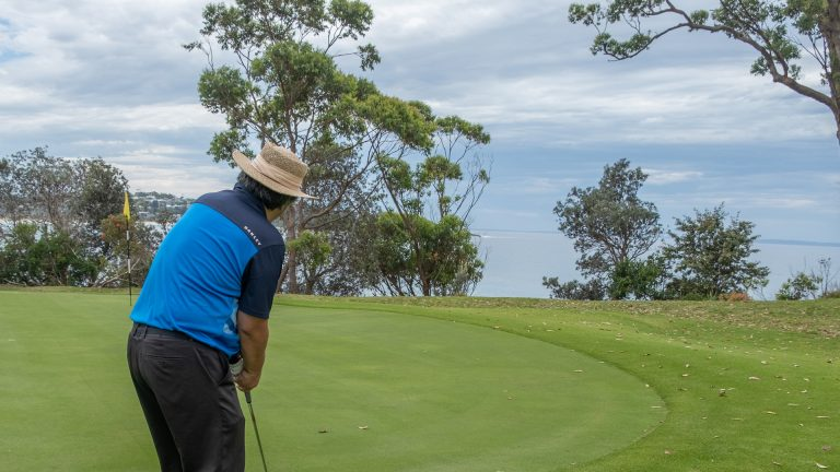 Aung playing golf at Mollymook